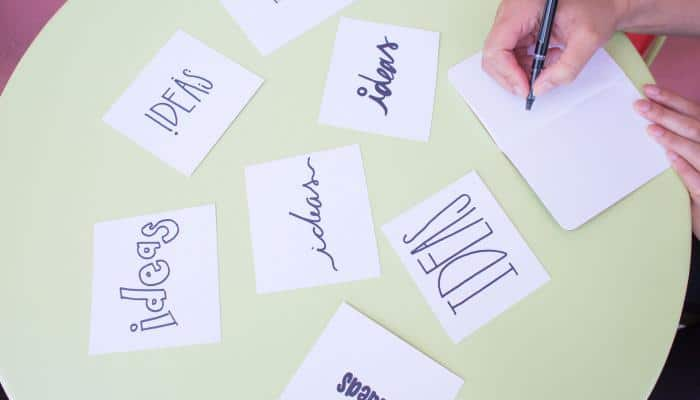 """Post it notes with the word """"ideas"""" written in different styles"""