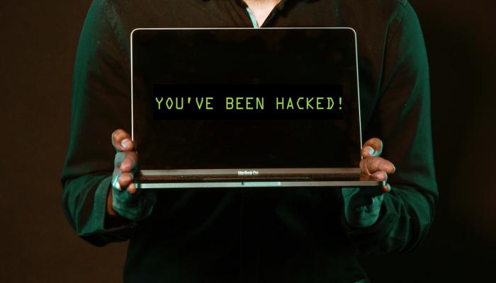 """Person holding laptop that says """"you've been hacked!"""""""